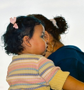 A child in the arms of a mother.